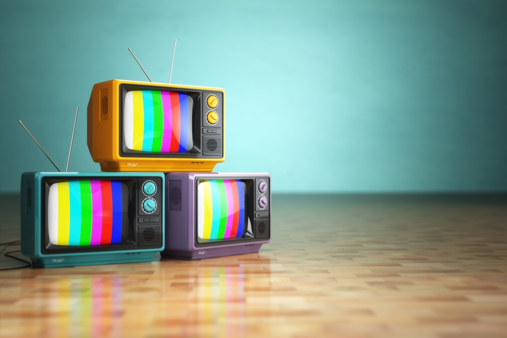 Vintage television concept. Stack of retro tv set on green background. 3d