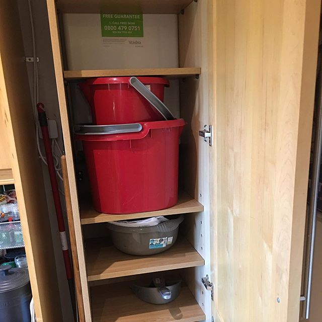 shelving and storage space in a kitchen cupboard around the gas boiler